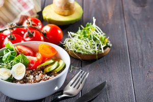 Fresh healthy salad with quinoa, cherry tomatoes and mixed greens, avocado, egg and micro greens on