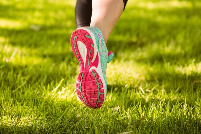 Woman in running shoes running on grass in the park