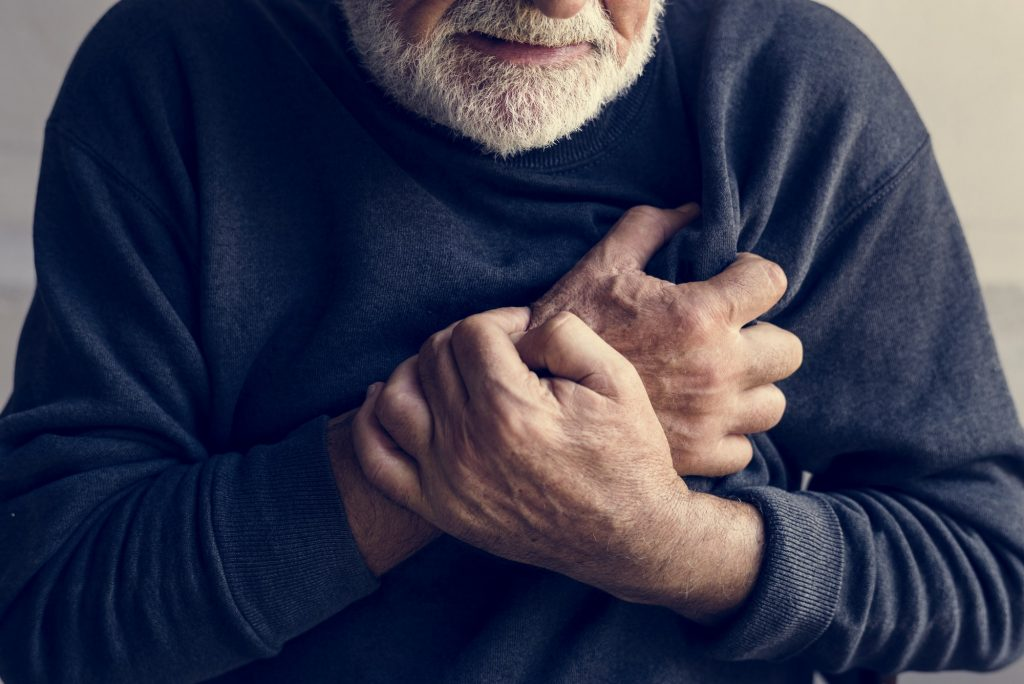 Close up of elderly man having a heart attack